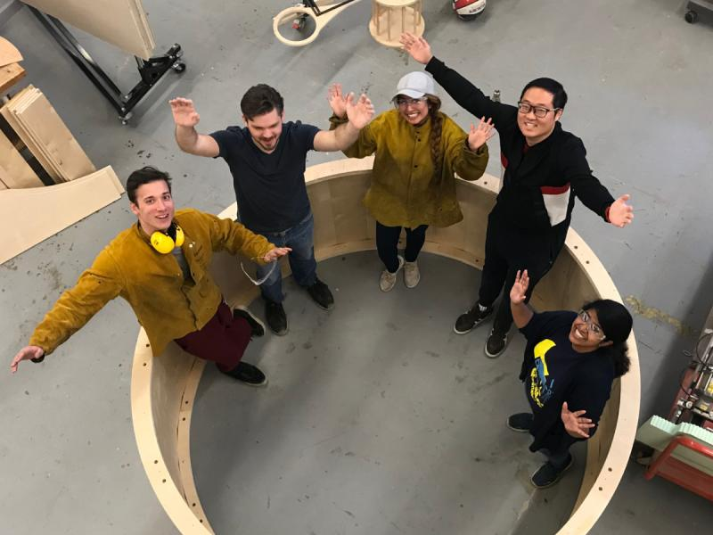 Students pose with a gigantic wheel they built.