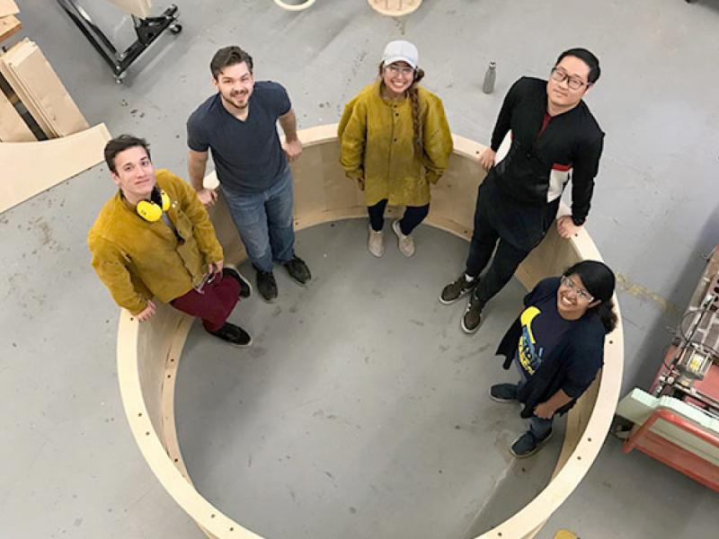 Students pose inside a gigantic wheel they fabricated.