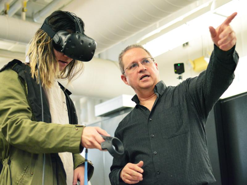 A professor points as a student wears a virtual reality headset.