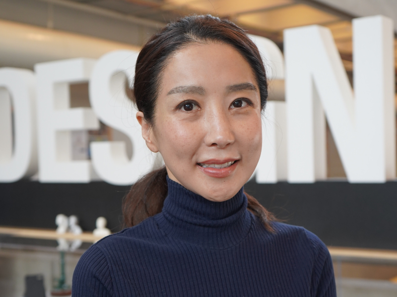 Young Mi Choi poses in front of letters that spell DESIGN.