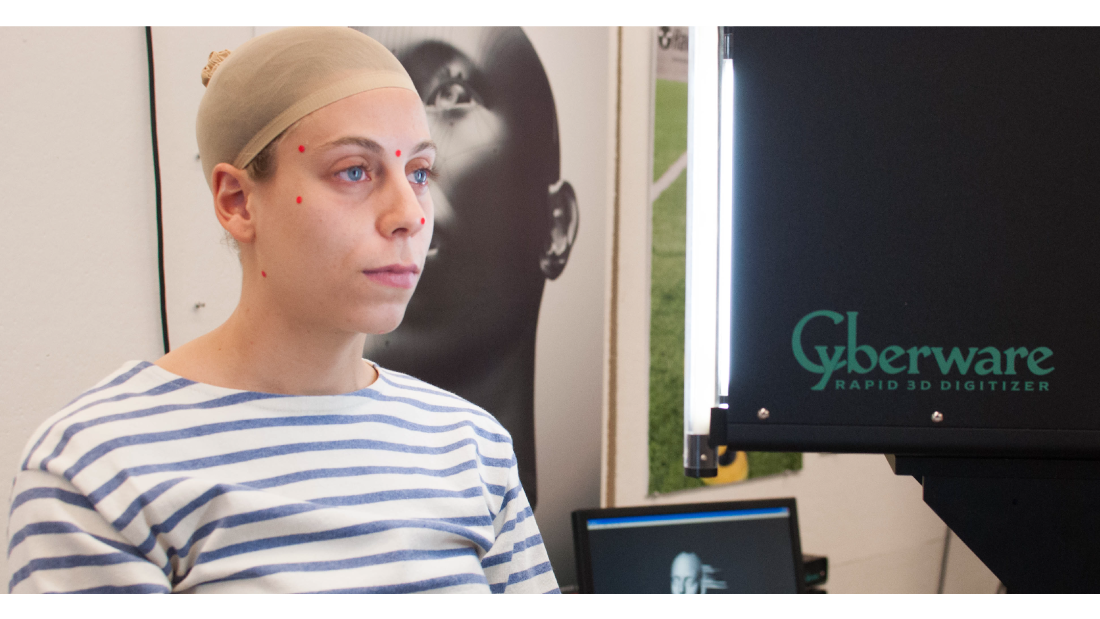 A student wears red dots on her face as she is scanned by a 3-D scanning machine.