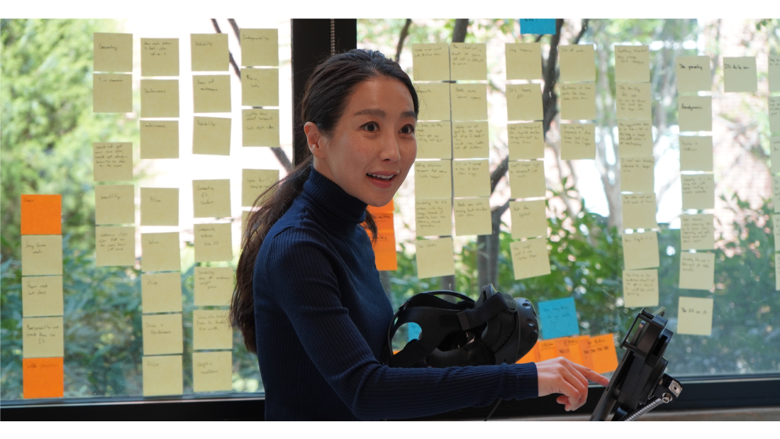 Professor Young-Mi Choi teaches a class in front of a window filled with sticky notes.