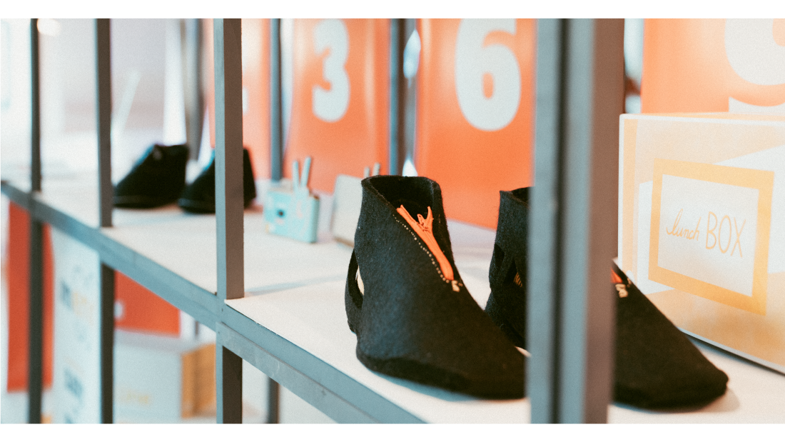 A pair of felt shoes made by students in an exhibition space.