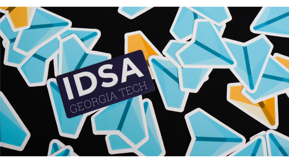 The IDSA logo on top of a colorful pattern of paper airplane designs.