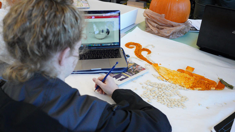 A student uses pumpkin parts to create an image for her pumpkin's design poster, based off a Bauhaus teapot.