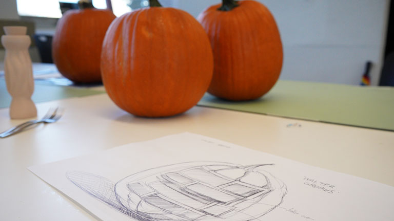 An industrial design student's sketch is ready to apply to a waiting pumpkin.