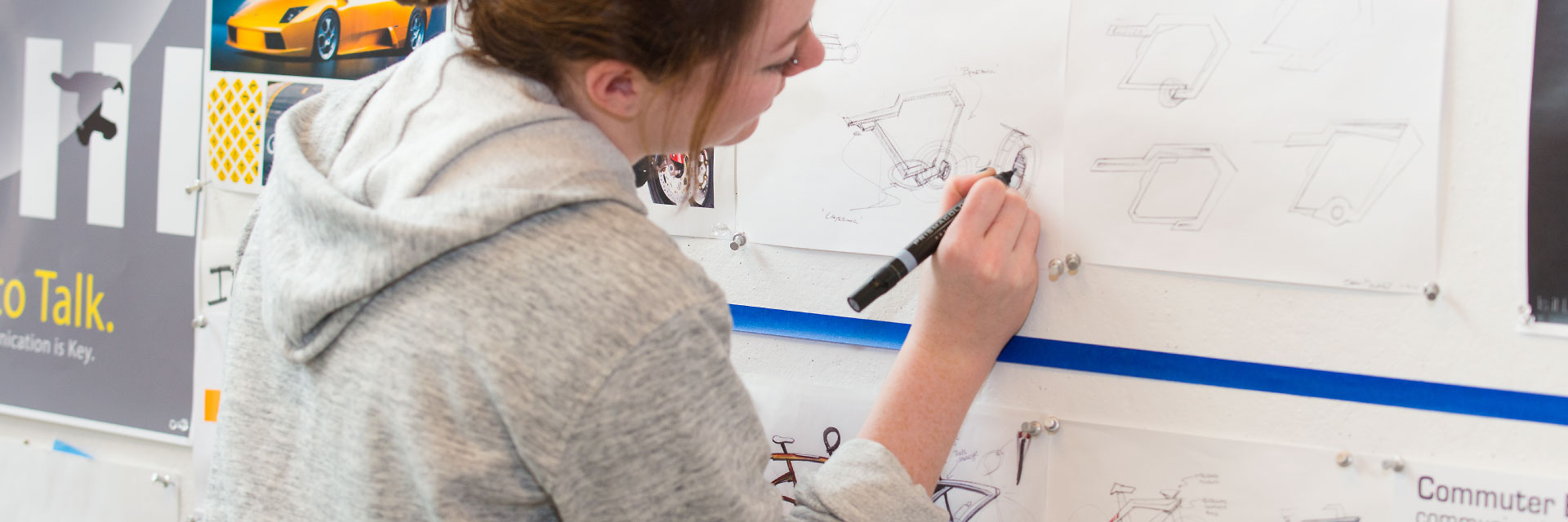 A student sketches on classwork that's pinned to a wall.